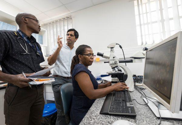 Satish Gopal, MD, MPH (center) with UNC-Project Cancer Program staff Tamiwe Tomoka (at microscope) and Edwards Kasonkanji (standing)