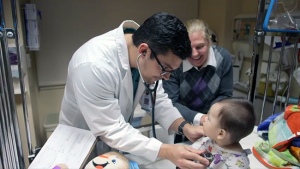 Kenan Primary Care Medical Scholar Daniel White examines a pediatric patient as Ansley Miller, pediatric course director, looks on. White is from Cherryville, where his father is a family medicine doctor.